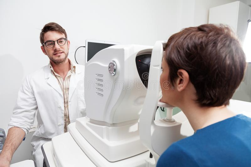 Eye Doctor is measuring a patient`s visual field. With the OCT test /Ophthalmologist in eyes clinic is doing diagnostic vision exam/ concept health and eyes stock image