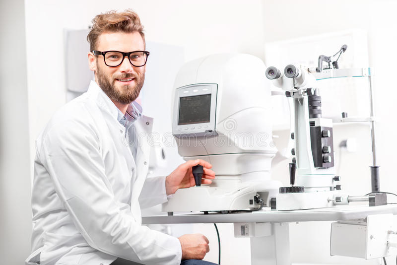 Eye doctor with ophthalmologic device stock images