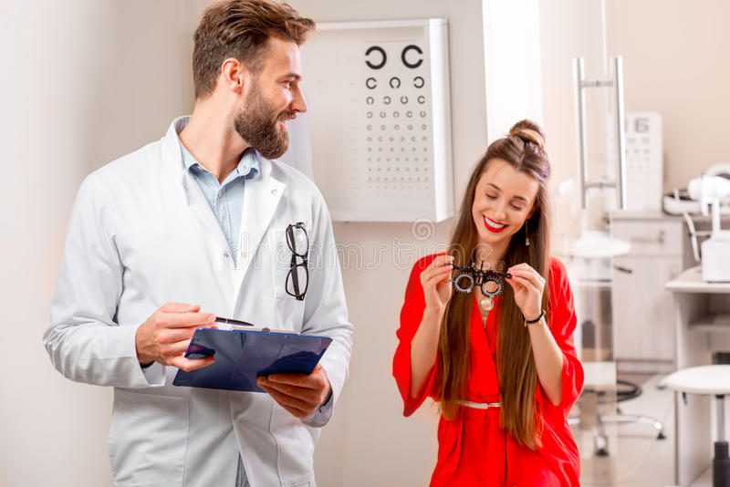 Eye doctor with patient. Eye doctor writing medical recipe standing in the cabinet with happy female patient royalty free stock photos
