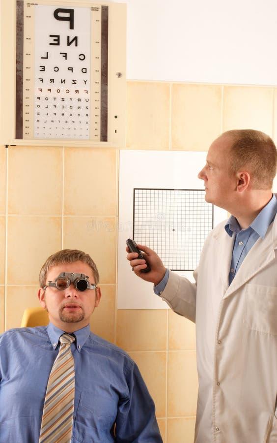Eye doctor performing eye examination stock photo