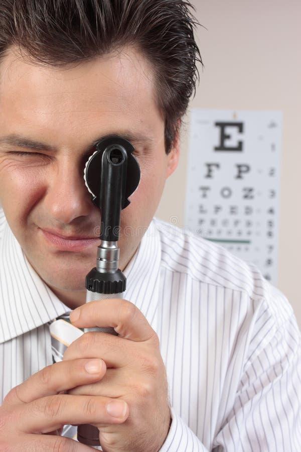 Eye doctor using opthalmoscope stock photos