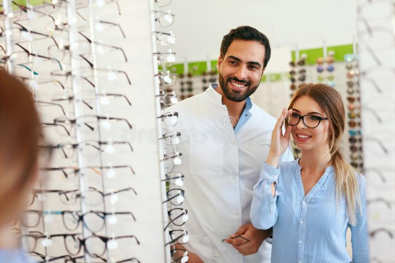 Eye Doctor With Woman Choosing Eyeglasses At Glasses Store. Female Trying On Glasses Near Mirror. High Resolution stock photography