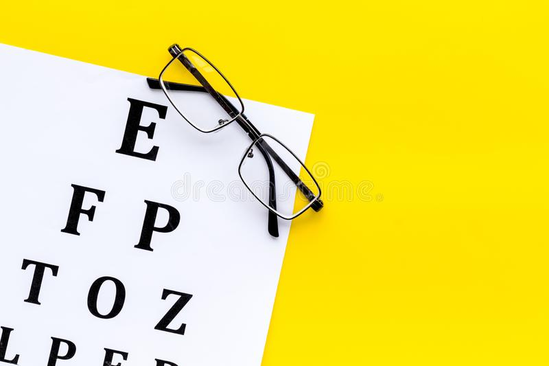 Eye examination. Eyesight test chart and glasses on yellow background top view copy space. Eye examination. Eyesight test chart and glasses on yellow background stock image