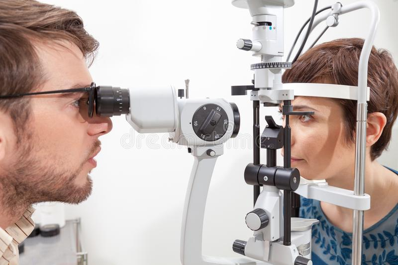Eye Examination with the Slit Lamp. Slit Lamp eye control with the Ophthalmologist /pretty women during an exam with Slit Lamp / the ophthalmologist in eyes royalty free stock images