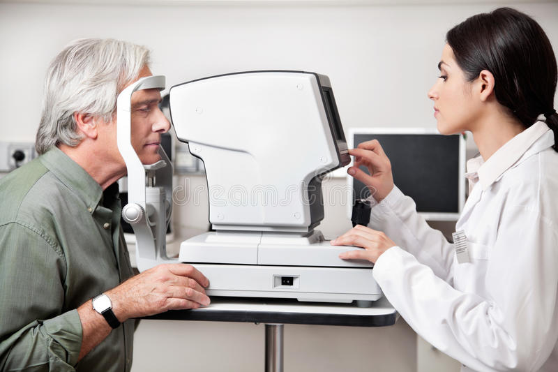 Eye Examination Through Visual Field Test. Young optometrist performing visual field test with an advance equipment royalty free stock photos