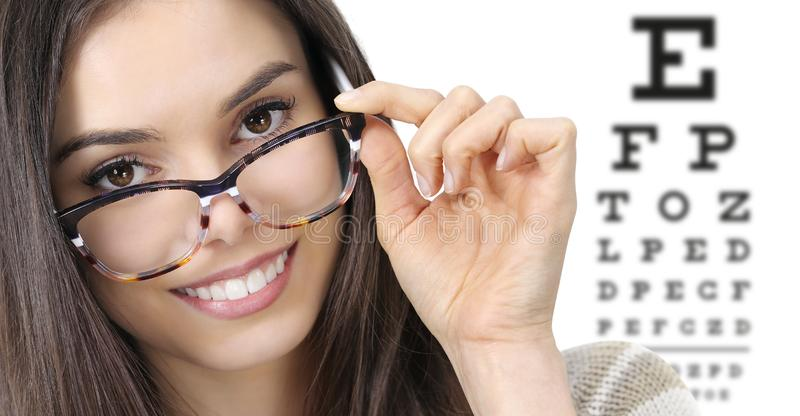 Eye examination, woman smiling with spectacles  in optician office with eye chart in white background, prevention and stock photography