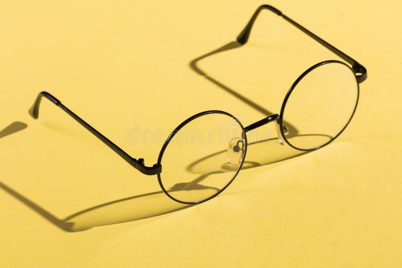 Eye glasses isolated on yellow background royalty free stock photography