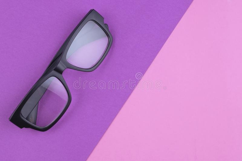 Eye glasses spectacles with shiny black frame on pastel color background stock photography