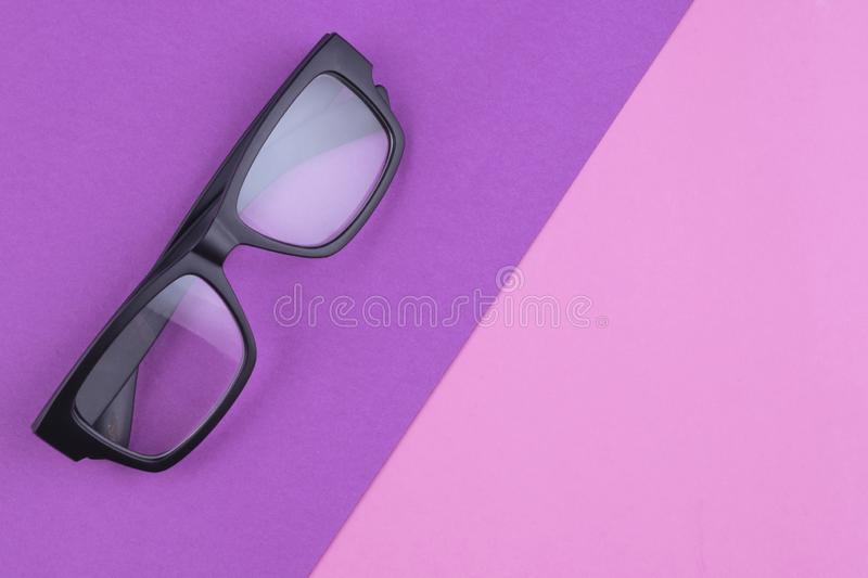 Eye glasses spectacles with shiny black frame on pastel color background stock image