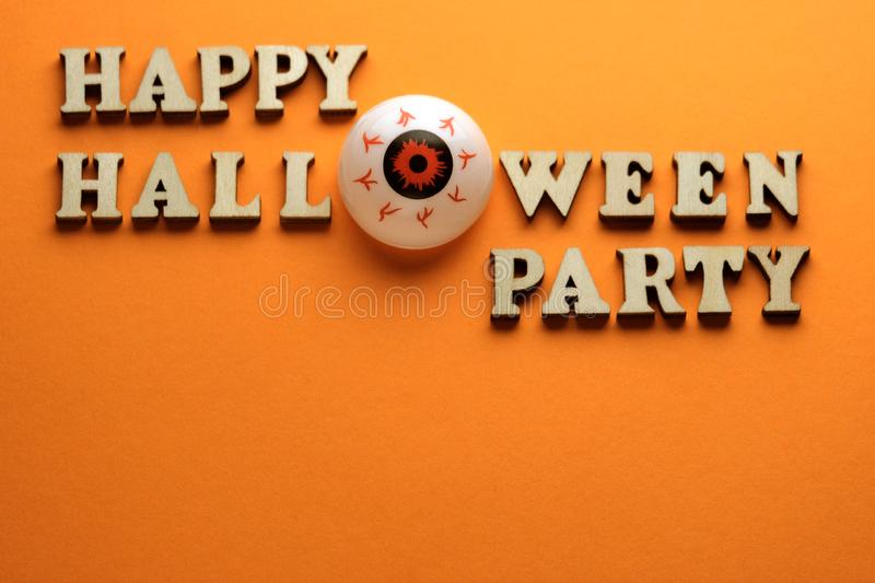 Eye instead of the letter O on a stylish inscription HAPPY HALLOWEEN PARTY. Wooden letters on a bright orange background. Template. For design for the holiday stock image