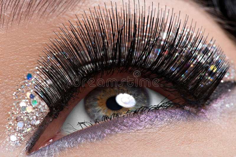 Eye with long black false eyelashes and creative fashion makeup. Closeup woman's eye with long black false eyelashes and creative fashion bright makeup stock photo