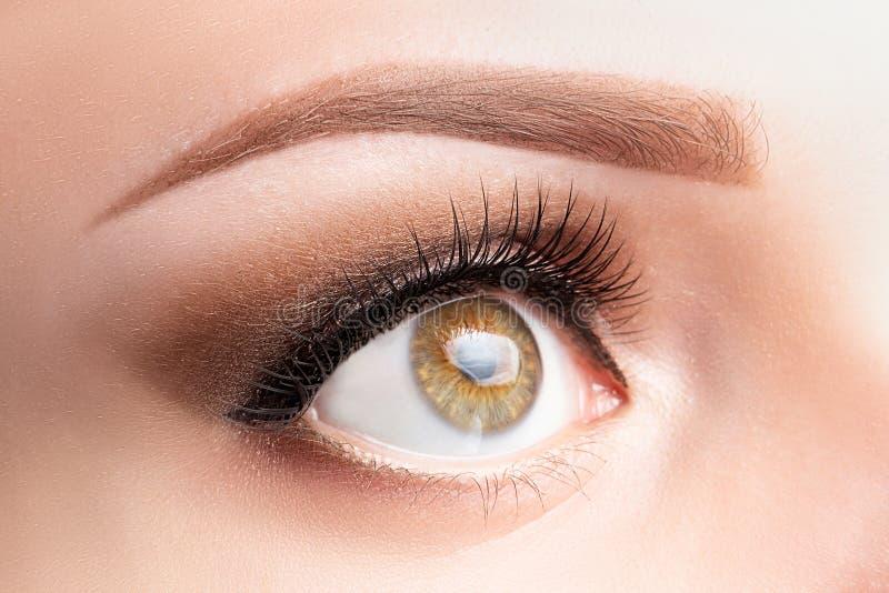 Eye with long eyelashes, beautiful makeup and light brown eyebrow close-up. Eyelash lamination, microblading, tattoo, permanent,. Cosmetology, ophthalmology royalty free stock images