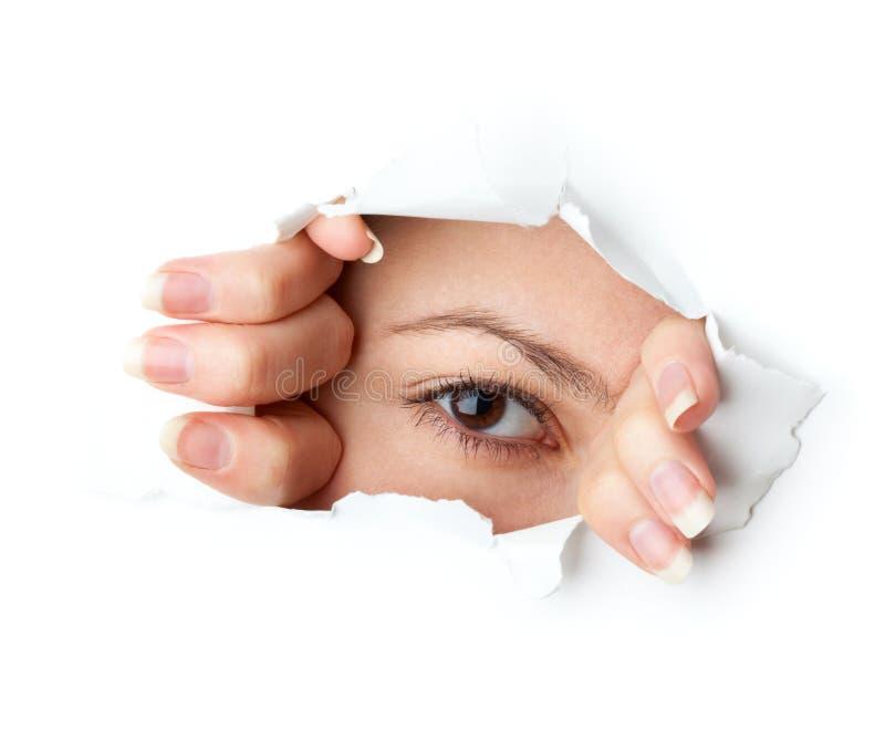 Eye looking through hole royalty free stock image