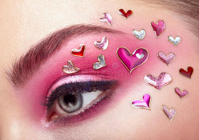 Eye make-up girl with a heart. Valentine`s day Makeup. Beauty Fashion. Eyelashes. Cosmetic Eyeshadow. Makeup detail. Creative Woman Holiday make-up royalty free stock photography