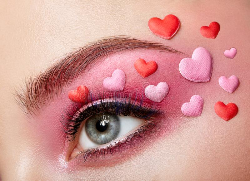 Eye make-up girl with a heart. Valentine`s day Makeup. Beauty Fashion. Eyelashes. Cosmetic Eyeshadow. Makeup detail. Creative Woman Holiday make-up stock photography
