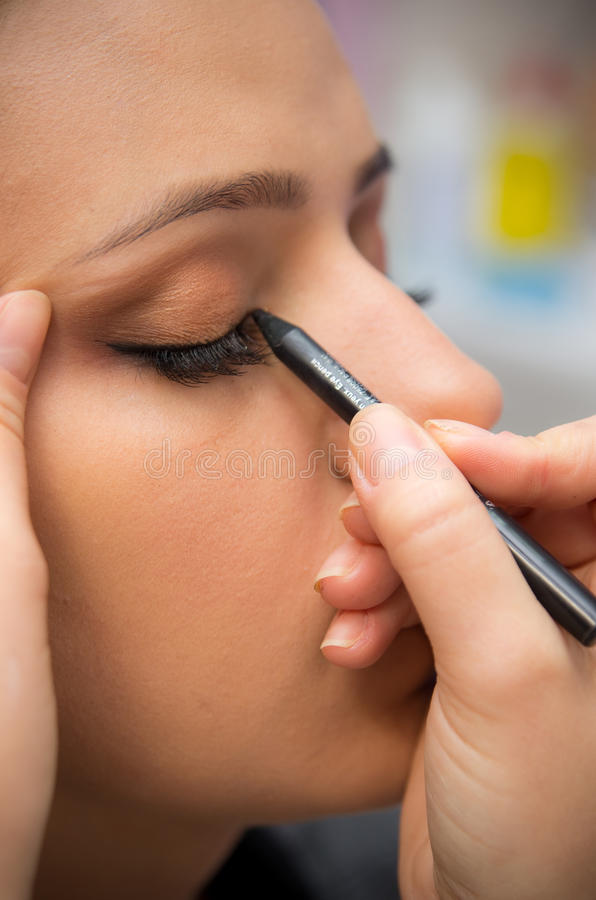 Eye makeup. A young beautiful woman having her eye makeup done. Makeup artist using the eyeliner tool stock images