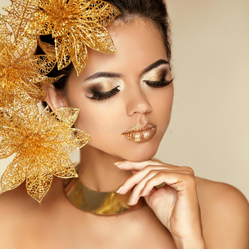 Eye Makeup. Beautiful Girl With Golden Flowers. Beauty Model Woman Face. Perfect Skin. Professional Make-up. Fashion Art Photo stock photo