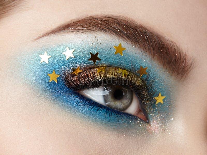 Eye makeup woman with decorative stars. Perfect makeup. Beauty fashion. False Eyelashes. Cosmetic Eyeshadow. Make-up detail. Eyeliner. Creative make-up the stock photography