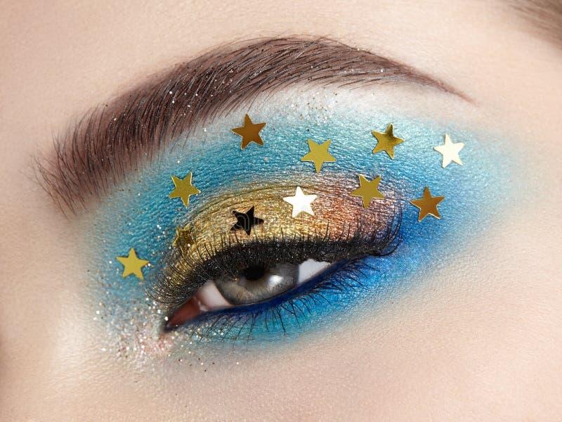 Eye makeup woman with decorative stars. Perfect makeup. Beauty fashion. False Eyelashes. Cosmetic Eyeshadow. Make-up detail. Eyeliner. Creative make-up the stock photo