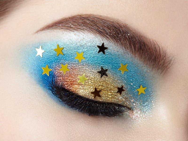 Eye makeup woman with decorative stars. Perfect makeup. Beauty fashion. False Eyelashes. Cosmetic Eyeshadow. Make-up detail. Eyeliner. Creative make-up the stock images