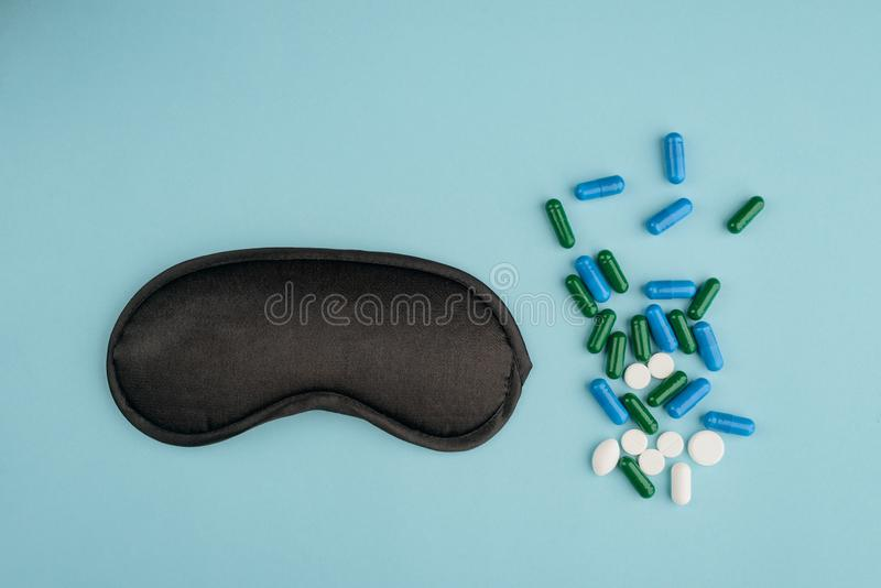 Eye mask and various pills. On blue background. Coping with sleep disorder and having a good night`s rest royalty free stock images