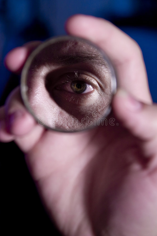 Eye in the mirror. Hand holding mirror, eye reflected in it