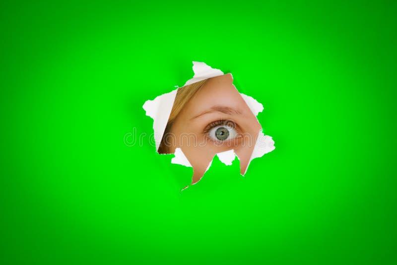 Eye peeping. Closeup of persons eye peeping through tear/hole in green background stock image