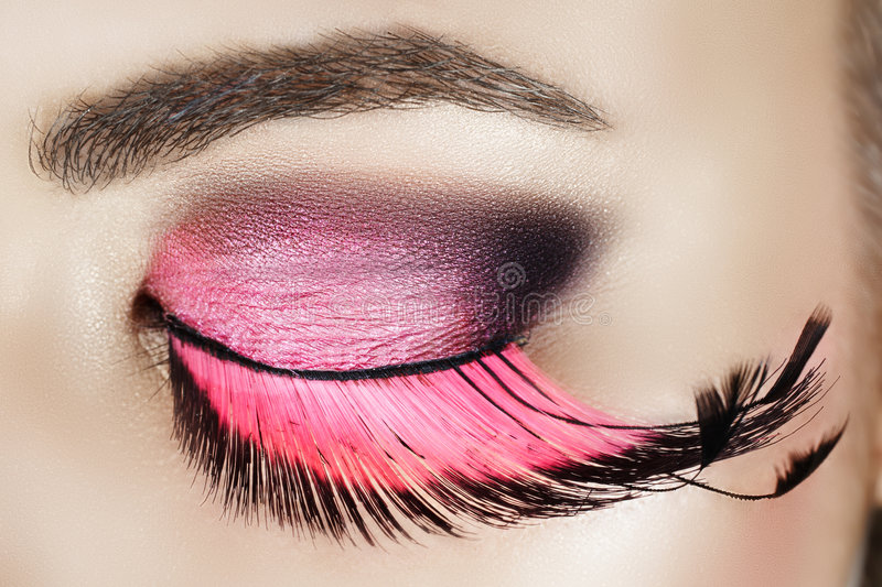 Eye with pink eyelashes. Macro eye of a woman with pink smoky eyeshadow with long feather false eyelashes