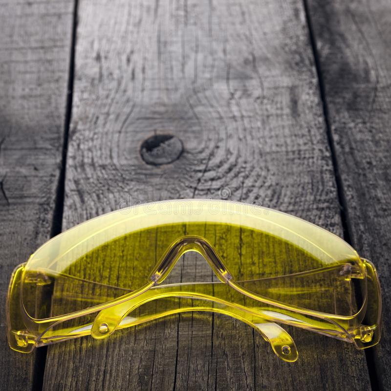 Eye protection glasses for repair and construction work, on a wooden background.  royalty free stock photography