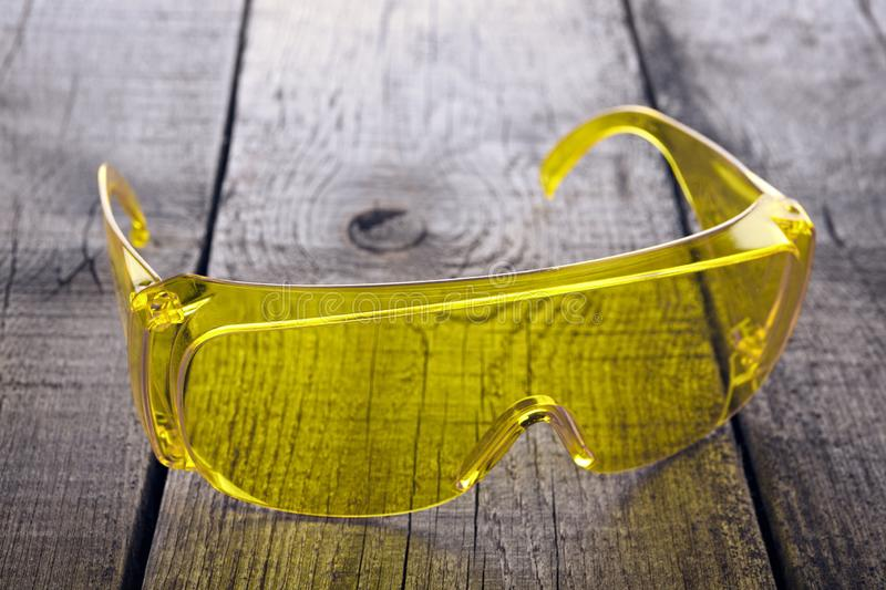 Eye protection glasses for repair and construction work, on a wooden background.  stock image