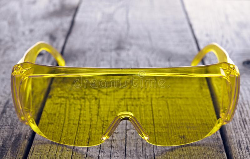 Eye protection glasses for repair and construction work, on a wooden background.  royalty free stock image