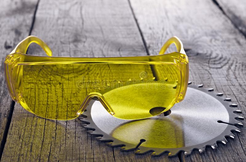 Eye protection glasses for repair and construction work, on a wooden background.  stock images