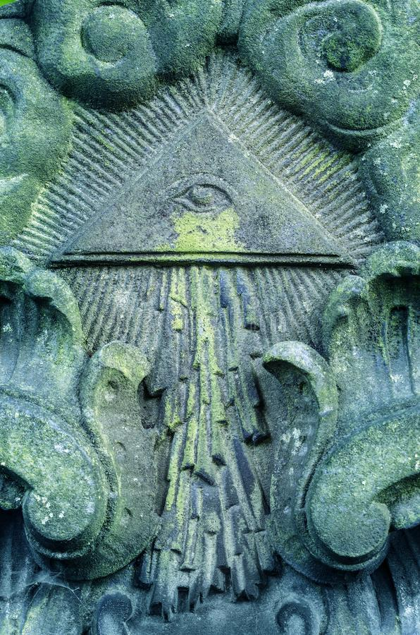 Eye of Providence. A weathered stone ancient relief with decorations stock image