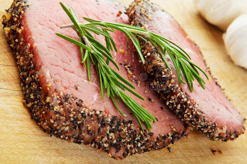 Eye of the round. Two raw, eye of round, Alberta beef steaks, with pepper & spices and topped with fresh rosemary royalty free stock photo