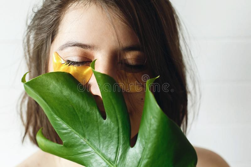Eye Skin Care and Treatment. Portrait of beautiful young woman with natural makeup and golden eye patches at green monstera leaf. royalty free stock photos