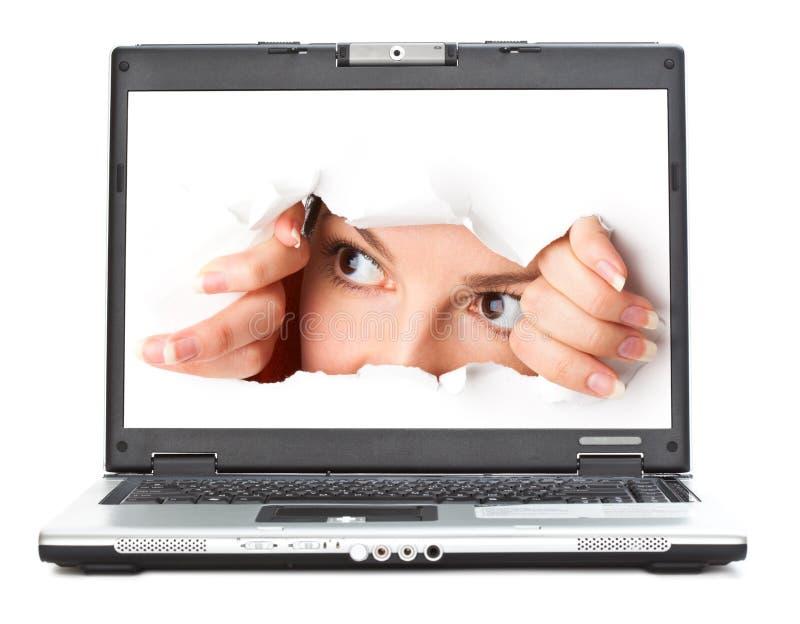 Eye a vista através do furo na tela do portátil imagens de stock