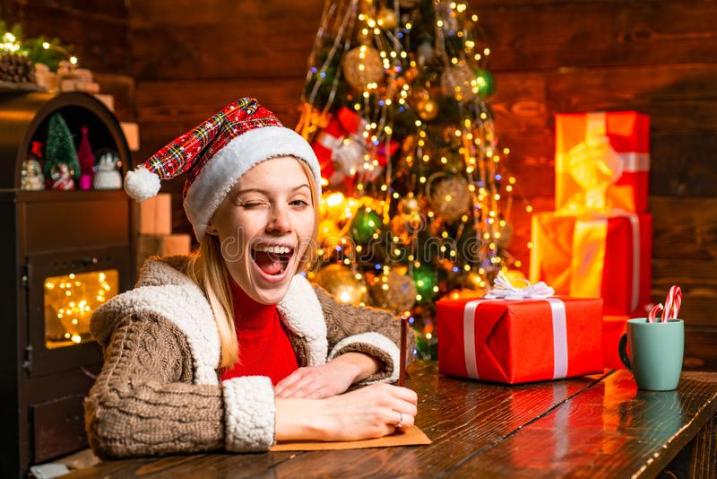 Eye winking blonde beautiful woman in Santa`s hat at winter holiday background. Merry christmas and happy new year. It. Is miracle. Concept of winter holidays royalty free stock photo