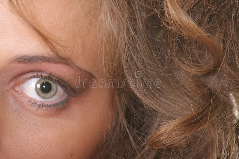 Eye of woman. Gray eye of woman and brown curled hairs closeup royalty free stock photos