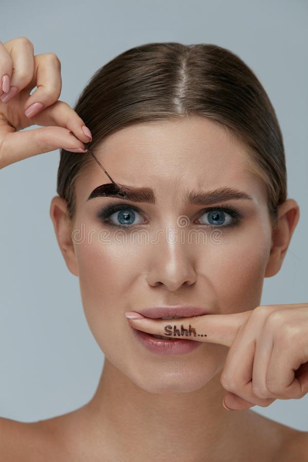 Eyebrow cosmetics. Woman taking off brow gel tint from eyebrow. Holding finger in mount with shhh letters on it closeup. Girl model peeling off beauty product royalty free stock photos