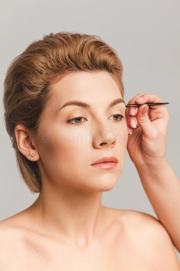 Eyebrow-korrigering med pincett, blond modellyta med makeup-nr Slutskott i studion arkivfoton