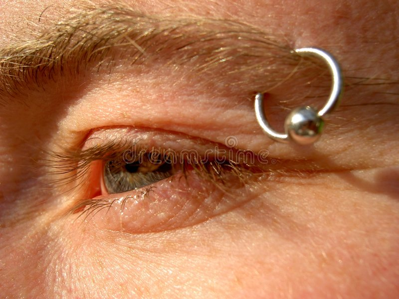 EyeBrow Piercing. Close up of a young man's eye and eyebrow piercing royalty free stock photos