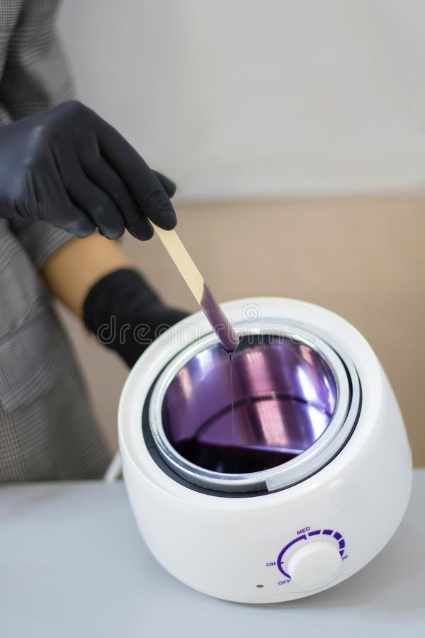 Eyebrow waxing. Hot wax of lilac color of a liquid consistence. Wax heater. Eyebrow waxing. Hot wax of lilac color of a liquid consistence stock photos