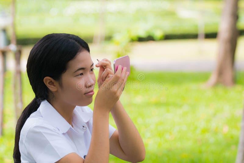 Eyebrown asiático de Makeup do estudante da beleza no parque imagens de stock royalty free