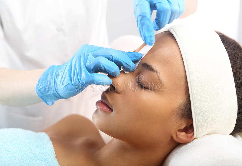 Eyebrows depilation with wax comb. Hair removal, eyebrow regulation wax in the beauty salon royalty free stock photo