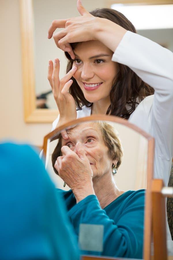 Eyecare Doctor Teaching Senior Woman To Insert royalty free stock photo