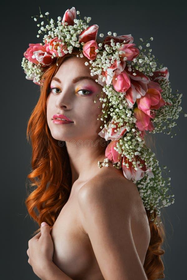 Eyed redhead κορίτσι με το φωτεινό makeup και ένα στεφάνι της ροής άνοιξη στοκ εικόνα