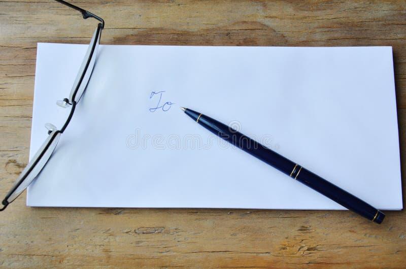 Eyeglass и ручка на белом конверте стоковое изображение