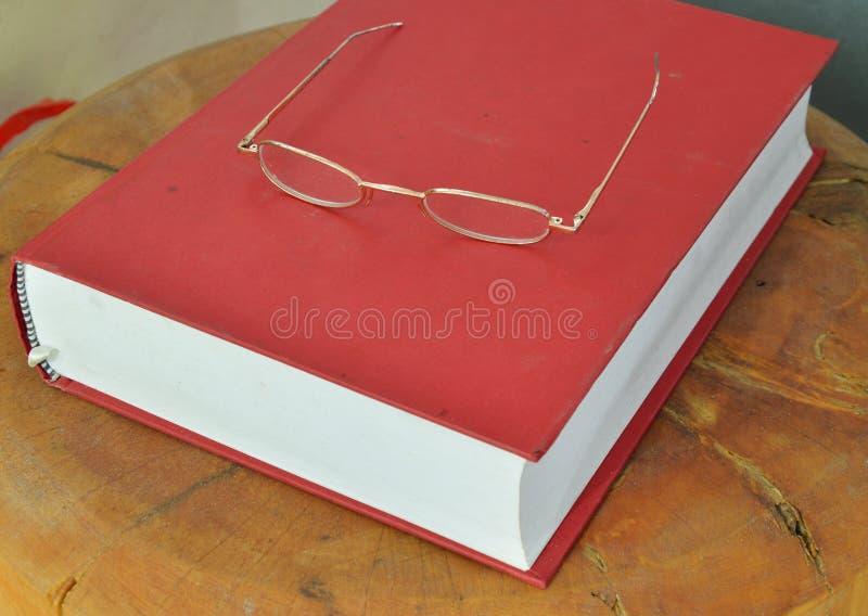 Eyeglass рамки золота на Красной книге стоковая фотография