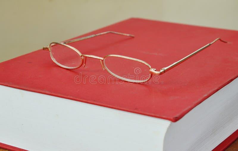 Eyeglass рамки золота на Красной книге стоковые фотографии rf