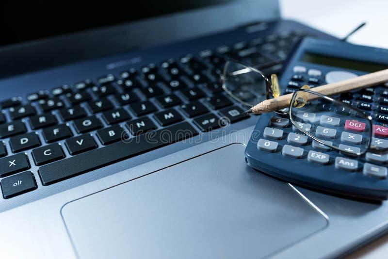 Eyeglass, ołówek, kalkulator na laptop klawiaturze, biznesowy tło wizerunek, obraz stock